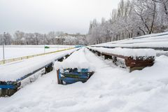 Benches covered with snow at the old stadium stock photo