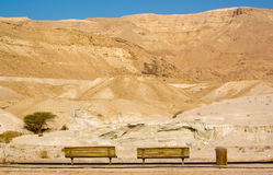 Benches in desert. Two wooden benches on the desert road on mountain backdrop Stock Photo