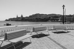 Benches on the embankment of Malta. Colorful park benches on the embankment of Valletta. Promenade on the background of the bay in Malta. Black and white picture Stock Image