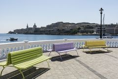 Benches on the embankment of Malta. Colorful park benches on the embankment of Valletta. Promenade on the background of the bay in Malta Stock Photo