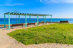Benches and green lawn on coastal promenade Stock Image
