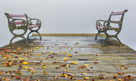 Benches on a jetty on a foggy autumn day. stock photography