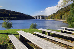 Benches on a lake with a view of highway bridge Stock Images