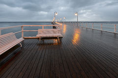 Benches and lamp posts on a pier Stock Photo