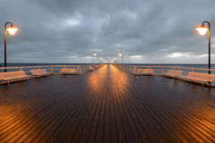 Benches and lamp posts on a pier Stock Image