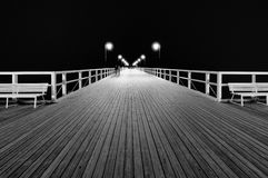 Benches and lamp posts on a pier at night. Royalty Free Stock Images