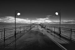 Benches and lamp posts on a pier Stock Images