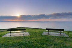 Benches near sea at sunset Royalty Free Stock Image