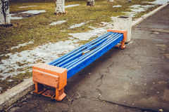 The benches in the old park. The beginning of spring. Snow and grass Royalty Free Stock Photo