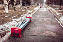 The benches in the old park. The beginning of spring. Snow and grass Royalty Free Stock Photos