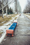 The benches in the old park. The beginning of spring. Snow and grass Stock Images