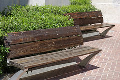 Benches in park. Two empty wooden benches near church in Lloret de Mar Stock Photo