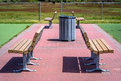 Benches in a park. A set of 4 benches on a brick walkway in a park Stock Image