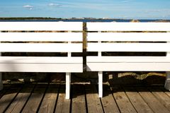 Benches. Picture of two white benches at a marina. Sea in the background Royalty Free Stock Photography