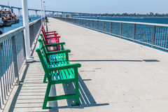 Benches on Pier at Cesar Chavez Park in San Diego. California, with Coronado Bridge and San Diego bay in the background Royalty Free Stock Photography