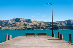 Benches on the pier. A pair of benches on the wooden pier in Akaroa, South Island, New Zealand Royalty Free Stock Images