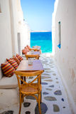 Benches with pillows in a typical greek bar in Mykonos with amazing sea view on Cyclades islands Royalty Free Stock Photo