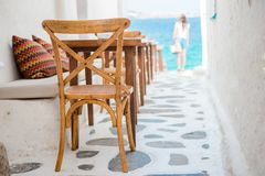 Beautiful typical greek outdoor cafe in Mykonos with amazing sea view on Cyclades islands. Benches with pillows in a typical Greek bar in Mykonos town with sea Royalty Free Stock Image
