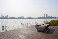 Benches on lakeside planked platform in sunny winter afternoon. Benches on planked platform at the lakeside in sunny winter afternoon,Chengdu,China royalty free stock photography