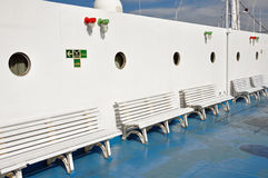 Benches and portholes on ship deck. Row of benches and portholes on ship deck painted with white and blue colors royalty free stock photo