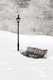 Benches in the snow. A slight sepia photo taken in winter where two antique style park benches next to the street lantern are surrounded with deep snow royalty free stock image