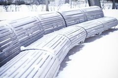 Benches standing in park and covered with snow Royalty Free Stock Image