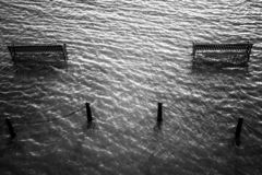 Benches surrounded in water. Benches surrounded in water with posts nearby royalty free stock photos