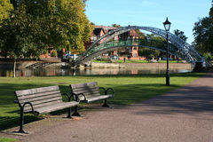 Benches by Suspension bridge at Bedford. Empty and peaceful benches in front of the suspension bridge across the river great ouse at Bedford, England, UK royalty free stock images