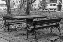 Benches, table and playground. Wooden benches, concrete table and a modest playground next to the old buildings in Serbia royalty free stock photo