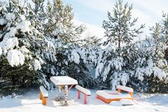 Benches with table in the snow. Beautiful winter landscape with snow covered trees and benches Royalty Free Stock Photo
