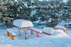 Benches with table in the snow. Beautiful winter landscape with snow covered trees and benches Royalty Free Stock Images