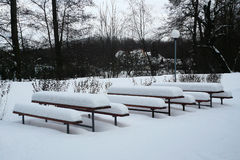 Benches and tables covered with snow. Next to the pub Royalty Free Stock Image