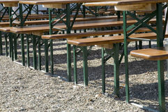 Benches and tables in german beer garden. Wooden benches and tables with metal legs on gravel gound Stock Image