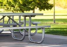 Benches and tables in the public park on the green meadow on a sunny day. Great for many people for the birthday party and. Celebrations stock images