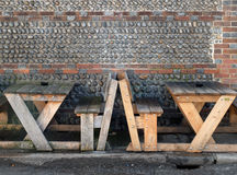 Benches and tables. Benches and wooden outside tables with flint wall Royalty Free Stock Photography