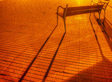 Benches and their shadows on a paved street Stock Photography