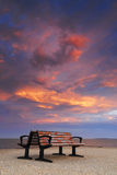 Benches under fiery sunset sky Stock Image