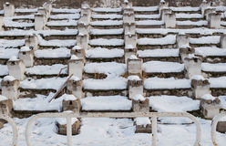 Benches under snow in an abandoned stadium. In the daytime Stock Photo