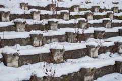 Benches under snow in an abandoned stadium. In the daytime Stock Image