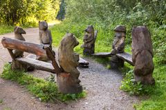 Benches with wooden sculptures of animals on terrenkur health trail along the Belokurikha mountain river. Belokurikha, Russia - July 30, 2015: Benches with Stock Photo