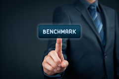 Benchmark. Concept. Businessman click on virtual button with text stock photography