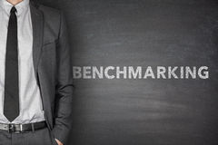 Benchmarking text on black blackboard. With businessman royalty free stock photo