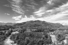 Bend of the river. At the foothills of Italian Alps in Piedmont.  Landscape on the background of of snow-capped peaks. Black and white picture Royalty Free Stock Image