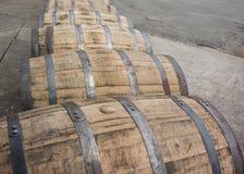 Bend in Row of Rolling Bourbon Barrels Stock Photo