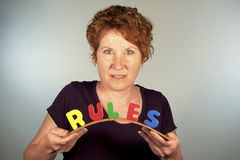 Bend the Rules. Smiling mature woman bending the word RULES Stock Photo