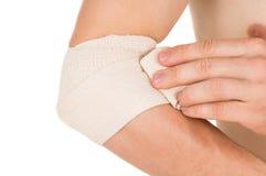 Bendaggio del gomito con una fasciatura elastica Fotografia Stock