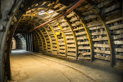 Bended corridor in modern mine. Fisheye view of bended corridor in modern coal mine, tracks and elements of internal infrastructure visible stock images