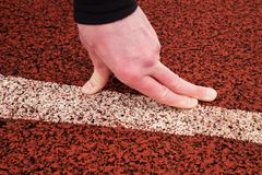 Bended fingers on start line, red rubber retrack Stock Photos