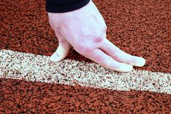 Bended fingers on start line, red rubber retrack. Bended fingers on start line, detailed red rubber retrack royalty free stock image