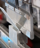 Bender at work. Close up to machine which bending metal sheet Royalty Free Stock Images